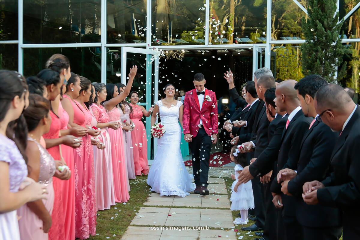 fotografia da saída dos noivos muito animada em um dia lindo de sol, com pétalas de flores
