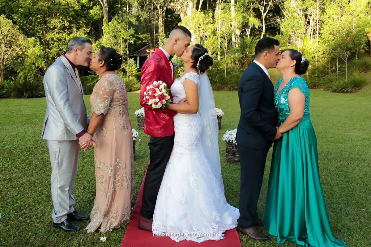 fotografia dos pais e os noivos dando um beijo mostrando a geração da família com muito amor e carinho e respeito1