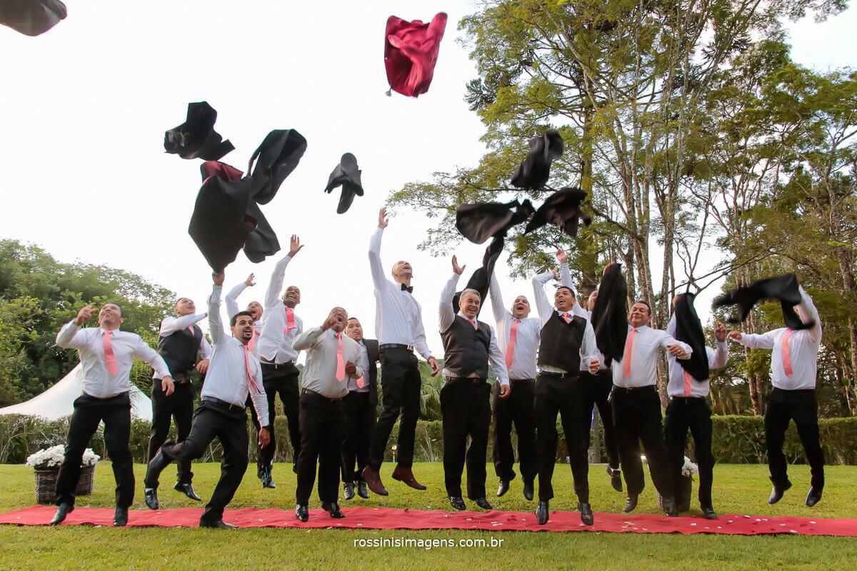 fotografia diferente espontânea, noivo e padrinhos jogando o terno para cima comemorando o casamento