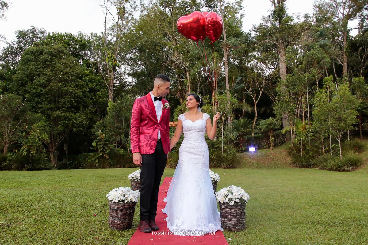fotografia de casamento, sessão de fotos do casal, noivo e noiva de mãos dadas com balões de corações