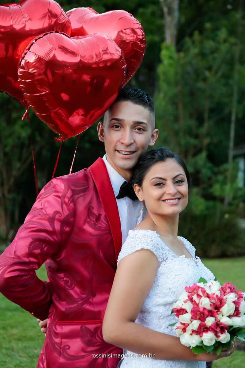 noivo abraçando a noiva segurando os baloes de coração