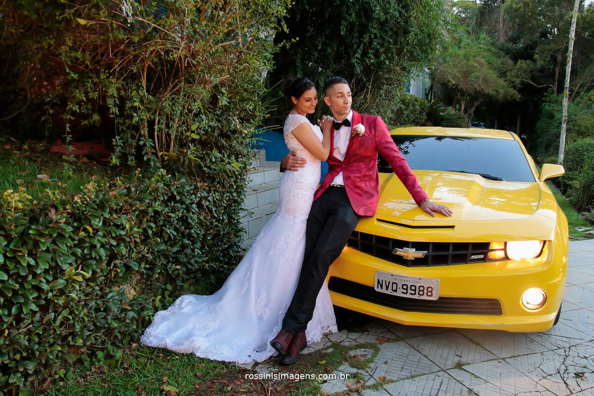 fotografia de casamento em mogi das cruzes, noivo com camaro amarelo, noivo de terno vermelho, noiva de vestido branco, eo o carro um lindo camaro amarelo Chevrolet