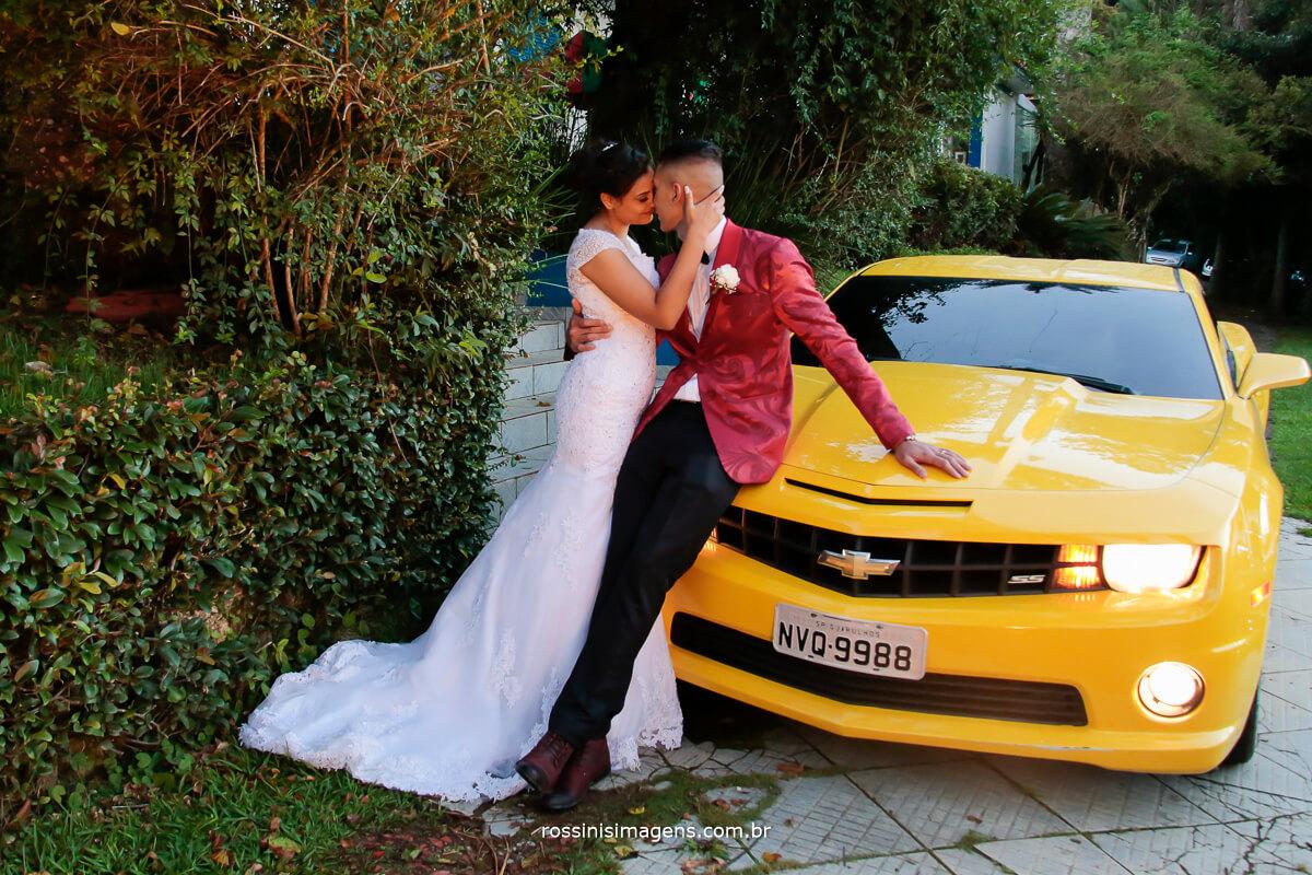 casal romântico curtindo enfrente o carro um camaro, fotografia de casamento rossini's imagens