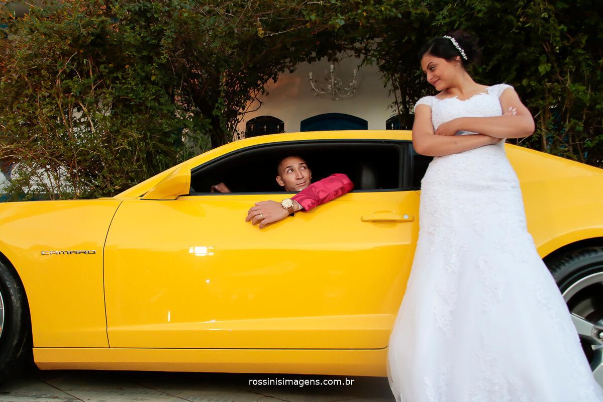 noivo de Camaro Amarelo e a noivi do lado de fora do carro de braços cruzado