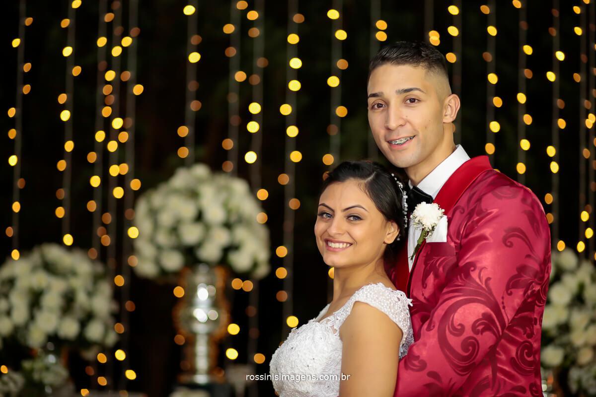 noiva e noivo enfrente a mesa do bolo na sessão de fotos