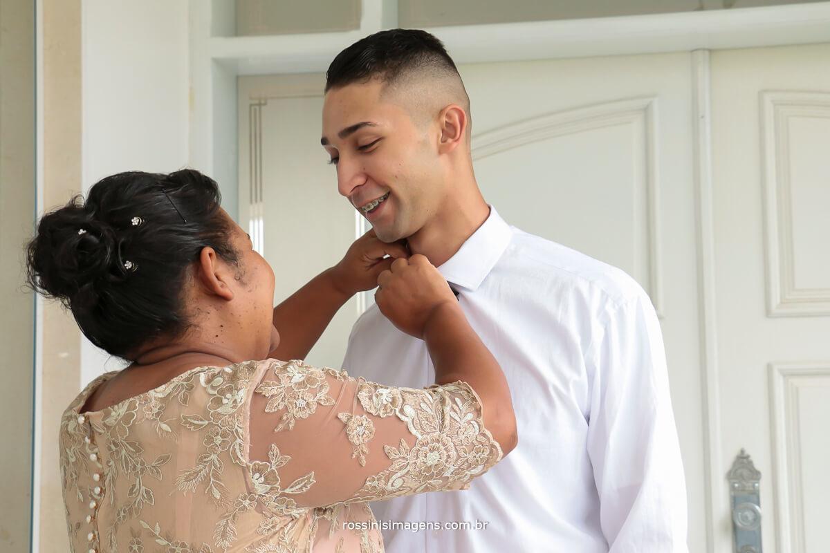 mãe no making of do noivo, família, mãe e filho, fechando o botão da camisa e colocando a gravata