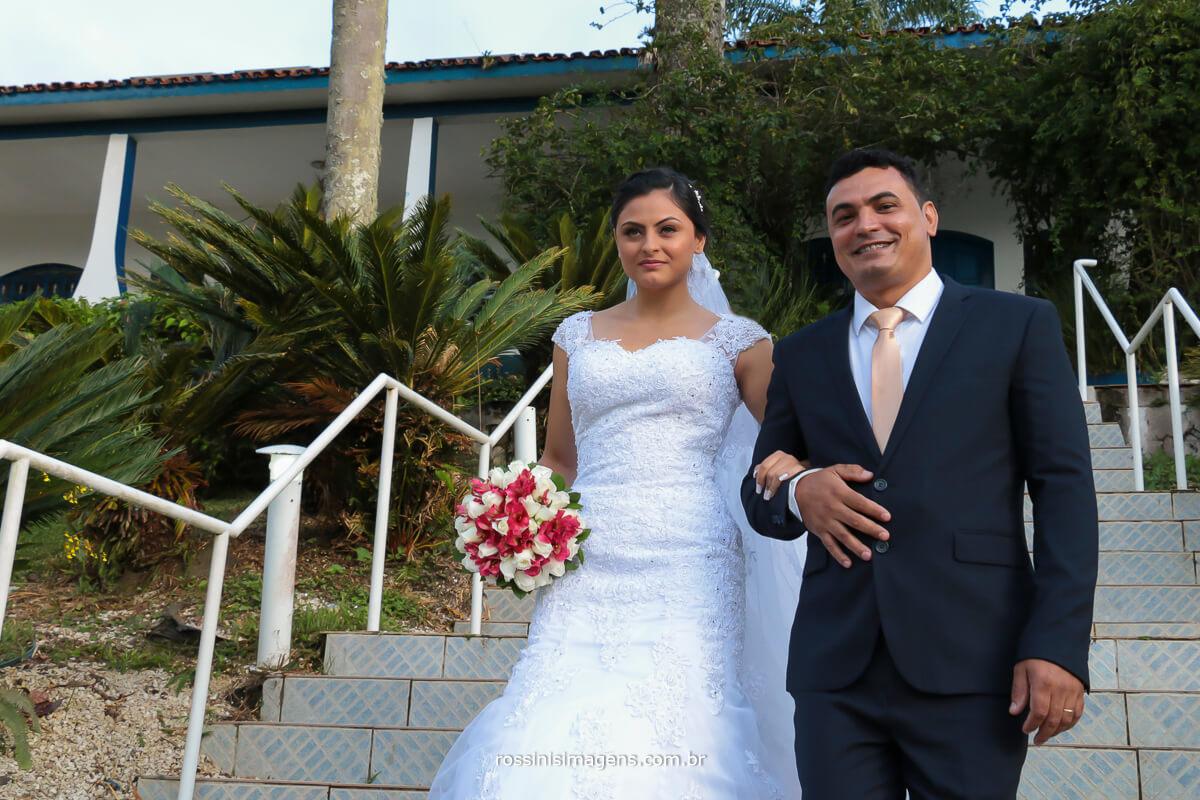 noiva com seu pai descendo as escadas, para a cerimonia de casamento