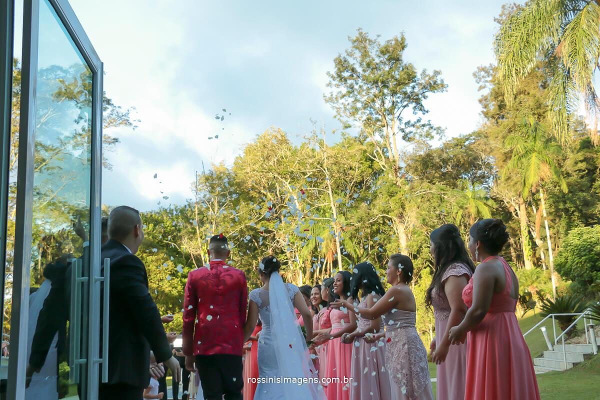 saída dos noivos de castas mostrando o ceu azul e as pétalas de flores lindo casamento