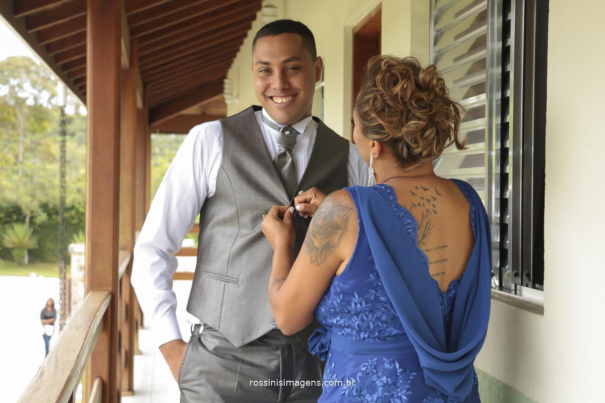 mãe do noivo fechando o colete, para o casamento
