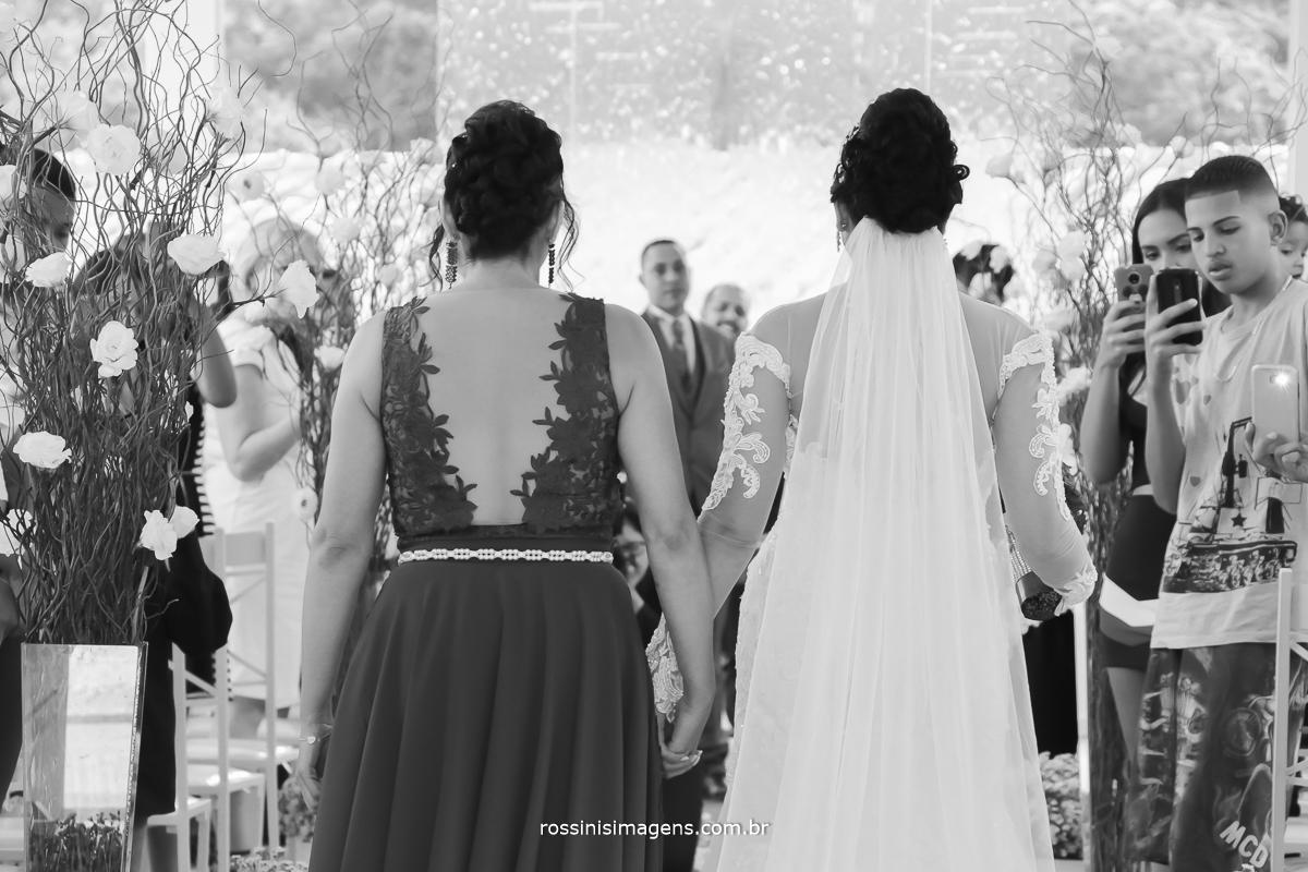 entrada da noiva de costa no corredor todo os detalhes do vestido e do véu
