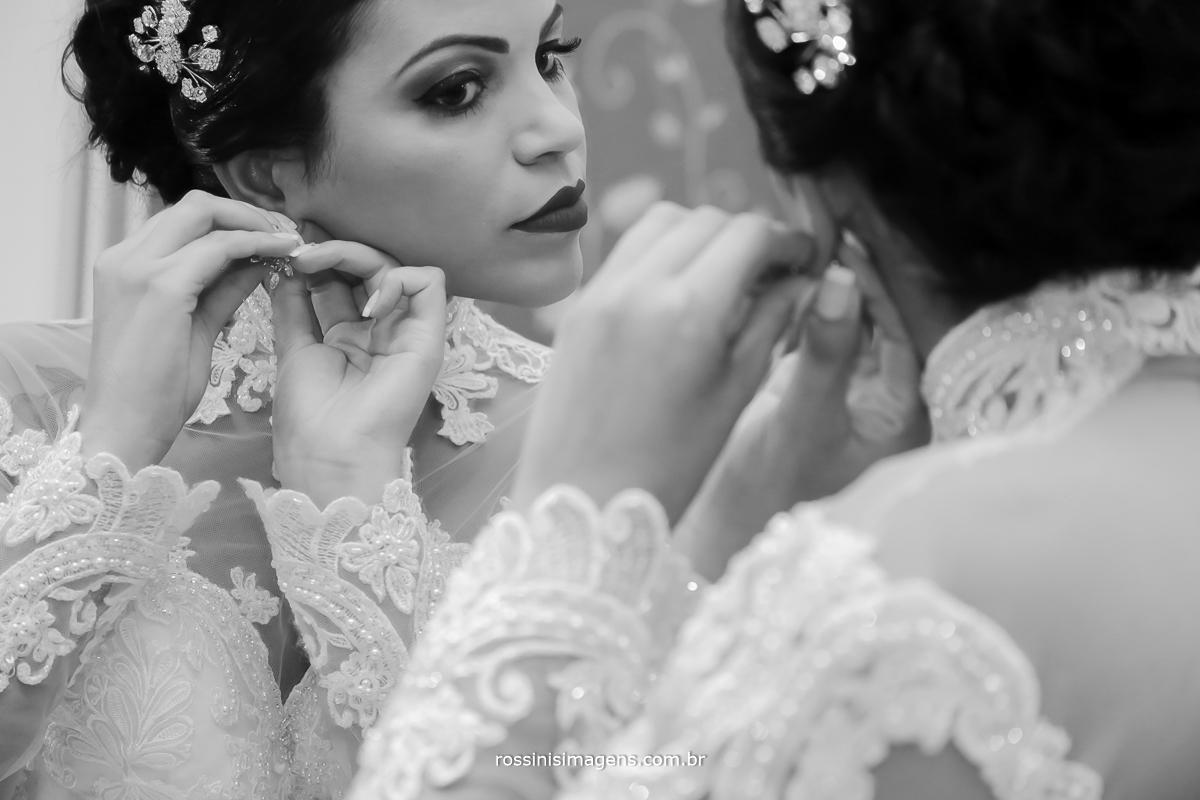 noiva colocando brinco enfrente ao espelho, noiva feliz contente alegre,