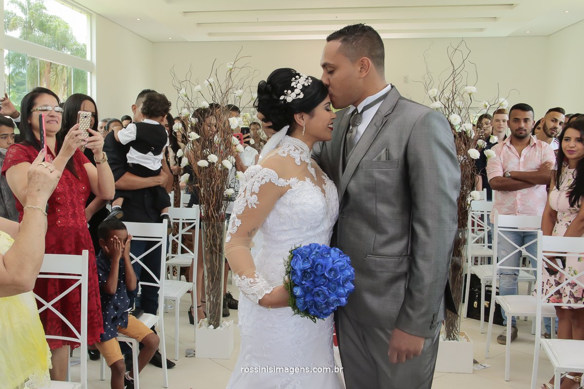 noivo e noiva no altar com um beijinho na testa da noiva com o seu lindo buquê azul