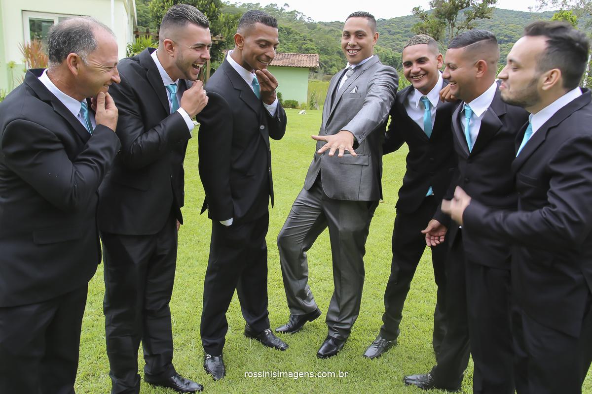 fotografia do noivo com os padrinhos , noivo mostrando a alianças e os padrinhos dando risada