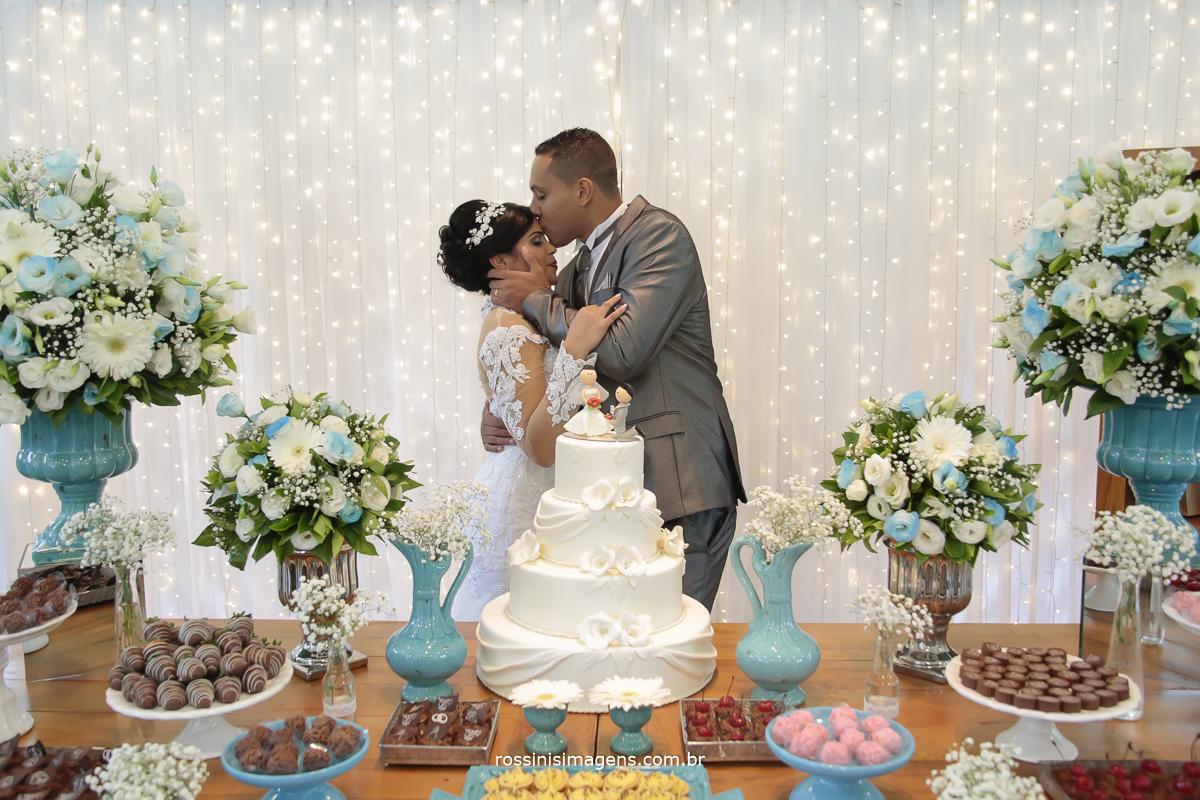 fotografia de casamento noivos na mesa do bolo com luz de led no fundo e a mesa bem decorada tudo feito pela Rogini Rosa decoração