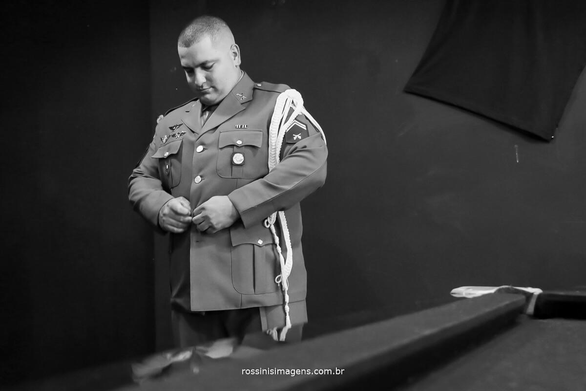 fotografia de noivo militar colocando traje festivo da corporação