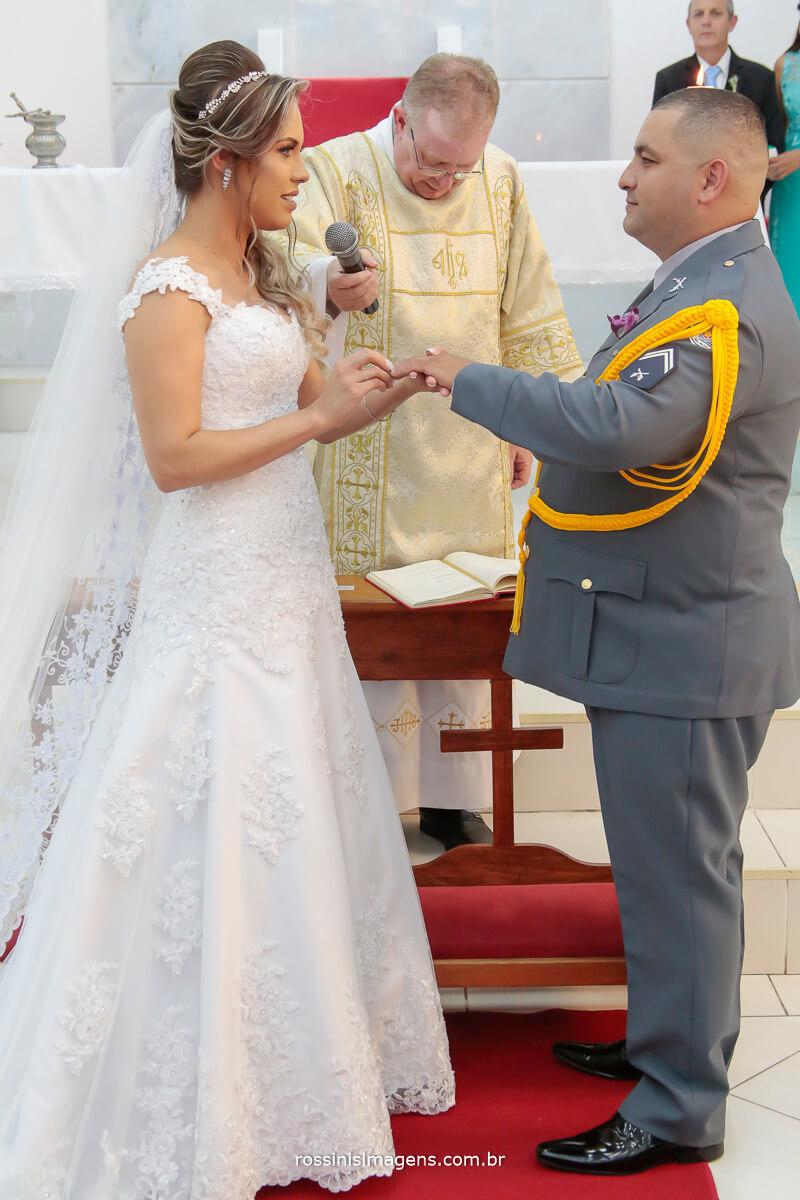 fotografia de noiva colocando a aliança no noivo tornando em tão marido e esposa