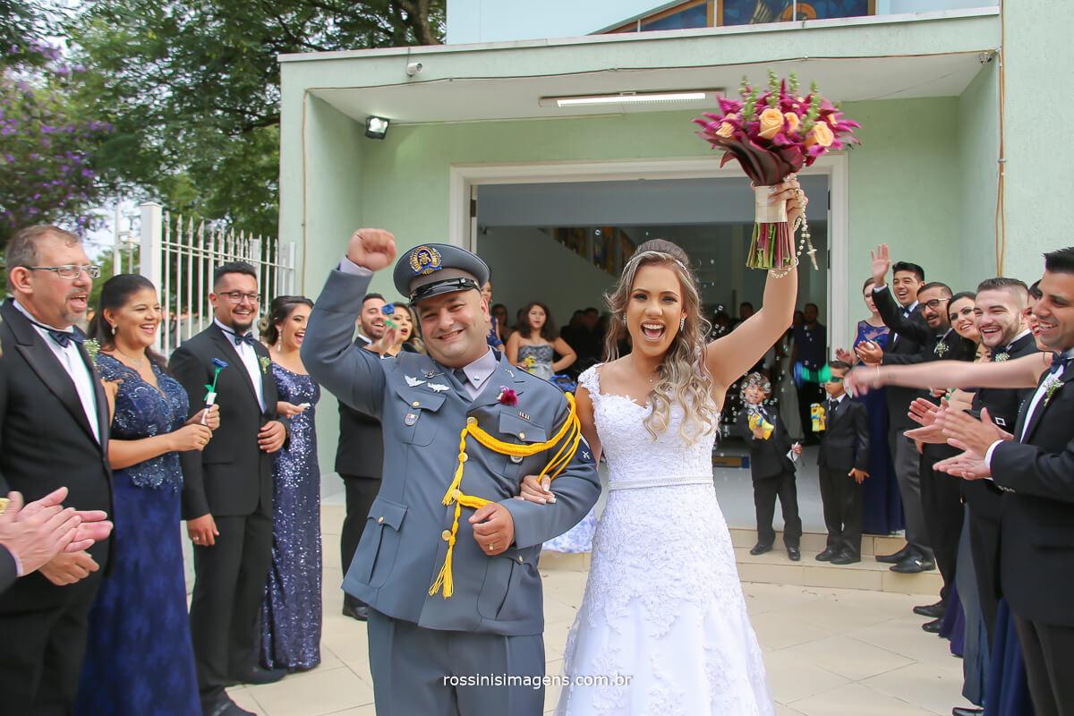 noivos comemorando na saída da igreja com os padrinhos