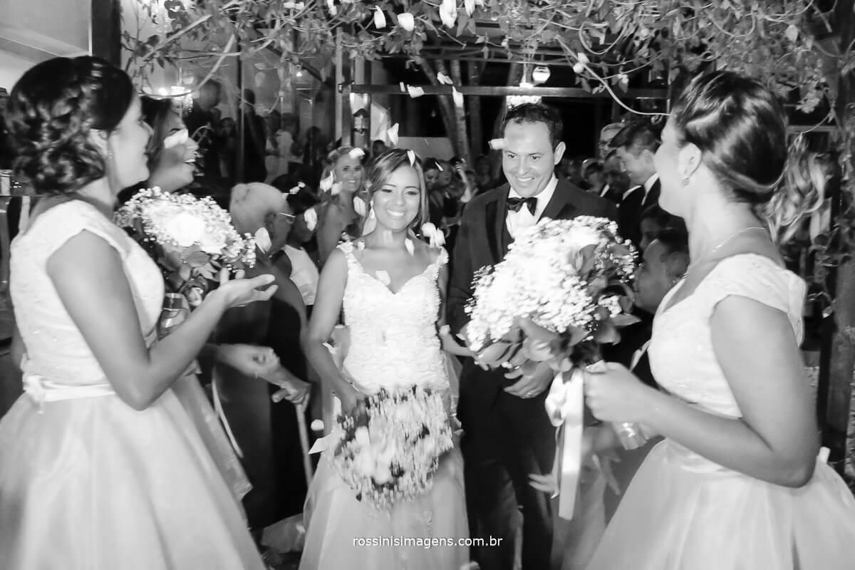 saída dos noivos com chuva de pétalas de flores, casal feliz e sorrindo