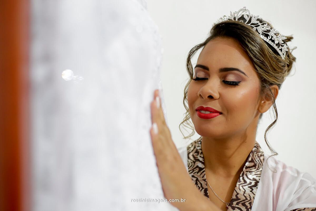 noiva tocando o vestido, sentindo toda a beleza em um toque, recordação para uma vida inteira, fotografia de casamento rossini's imagens, rossinis