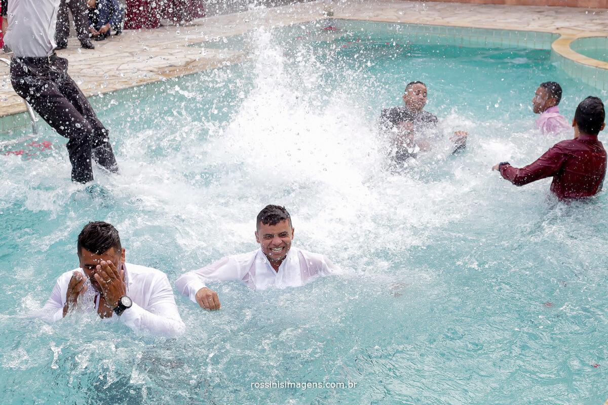 noivo pulando na piscina no casamento