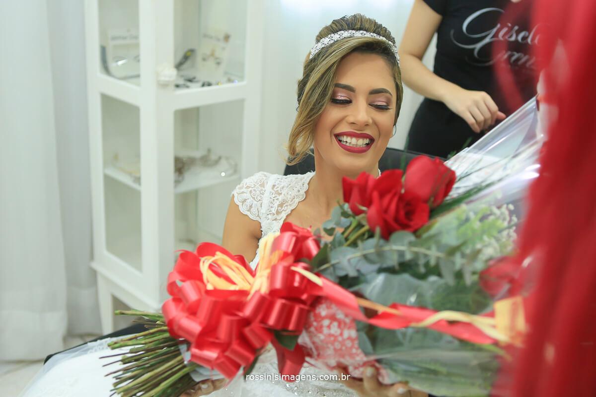 noiva muito feliz recebendo uma surpresa feita pelo noivo no making of um grande e lindo buque de rosas vermelhas feito pela celina flores
