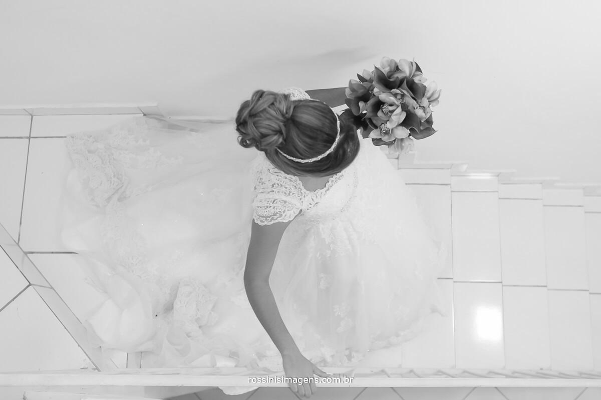 noiva descendo escada no making of com o buquê na mão fotografia criativa noiva indo para o casamento