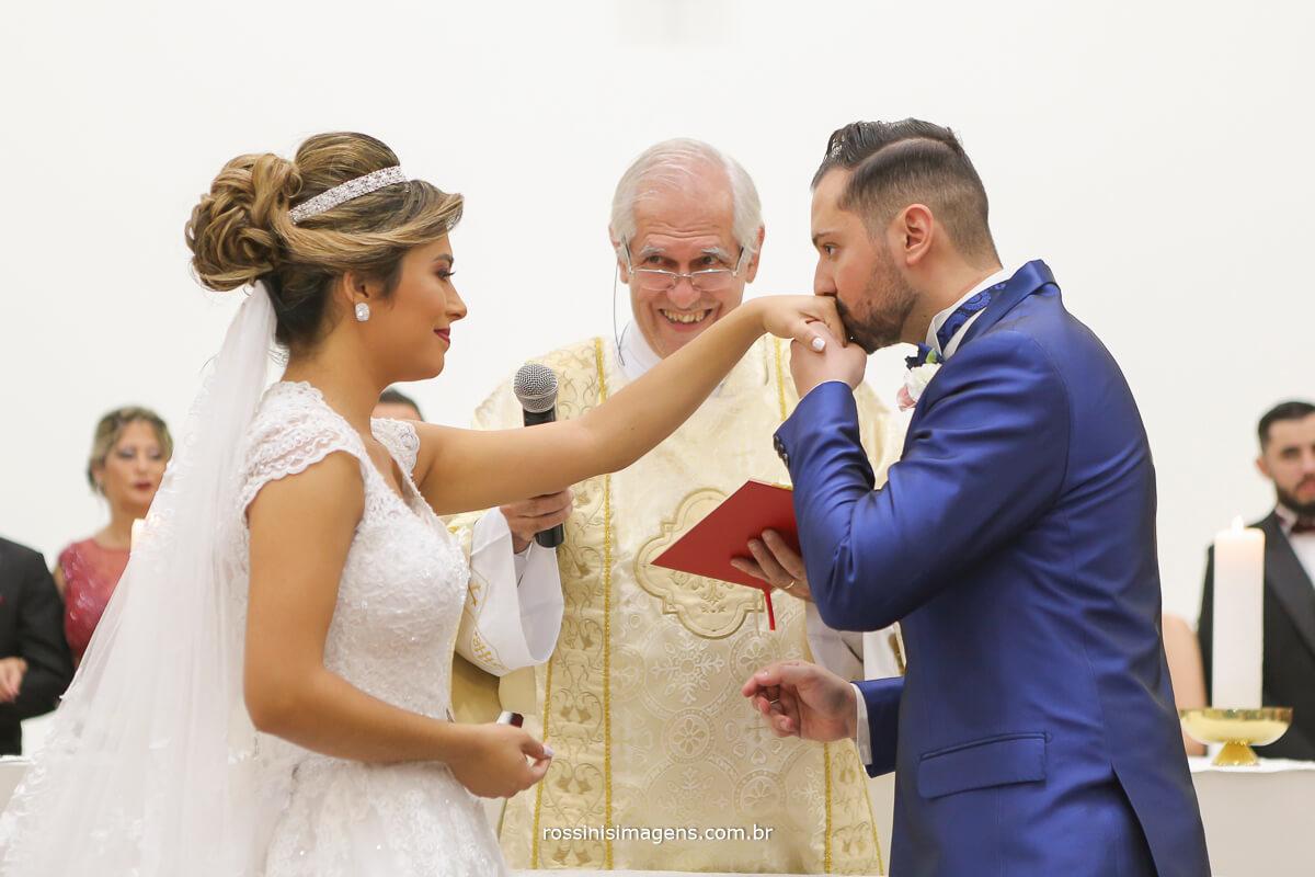 noivo beijando a aliança na mão da noiva