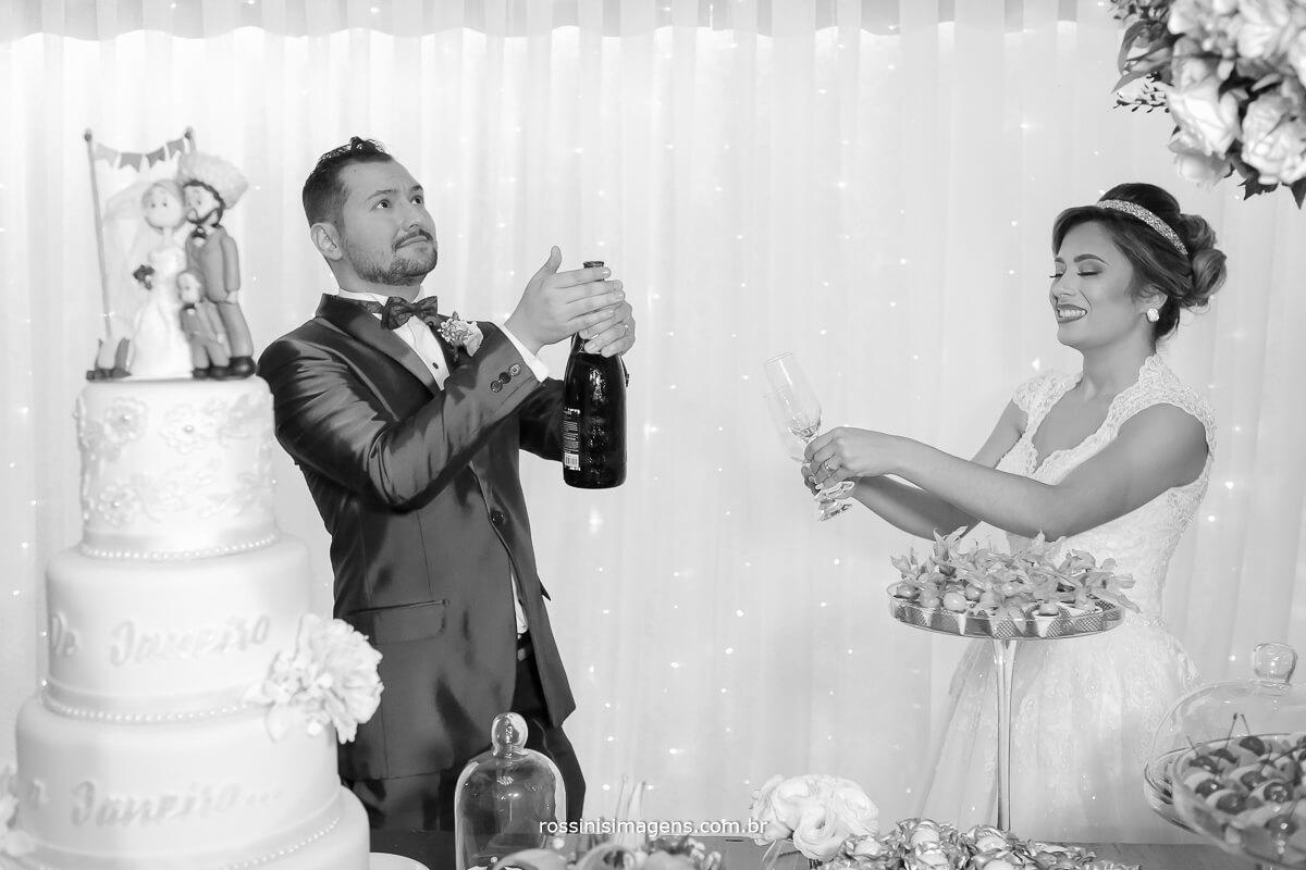 noivo abrindo champanhe na mesa do bolo