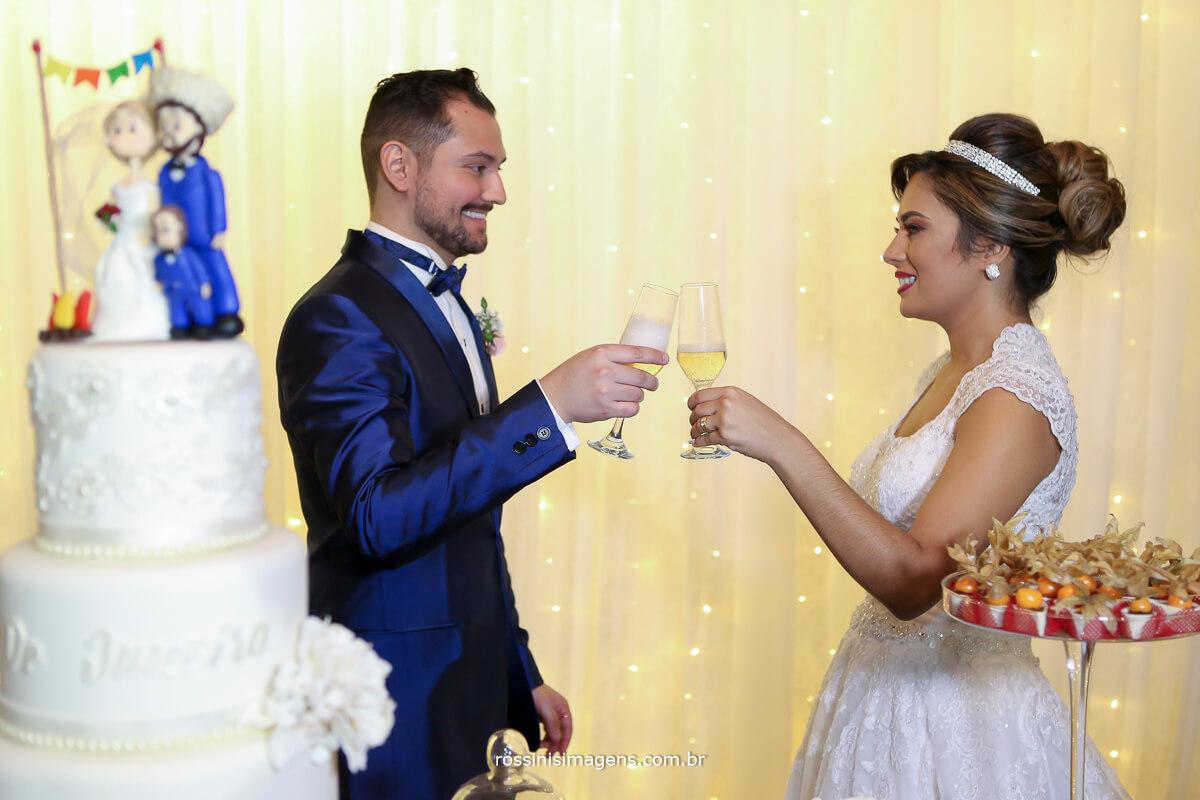 noivos fazendo o brinde na mesa do bolo com taca de champanhe