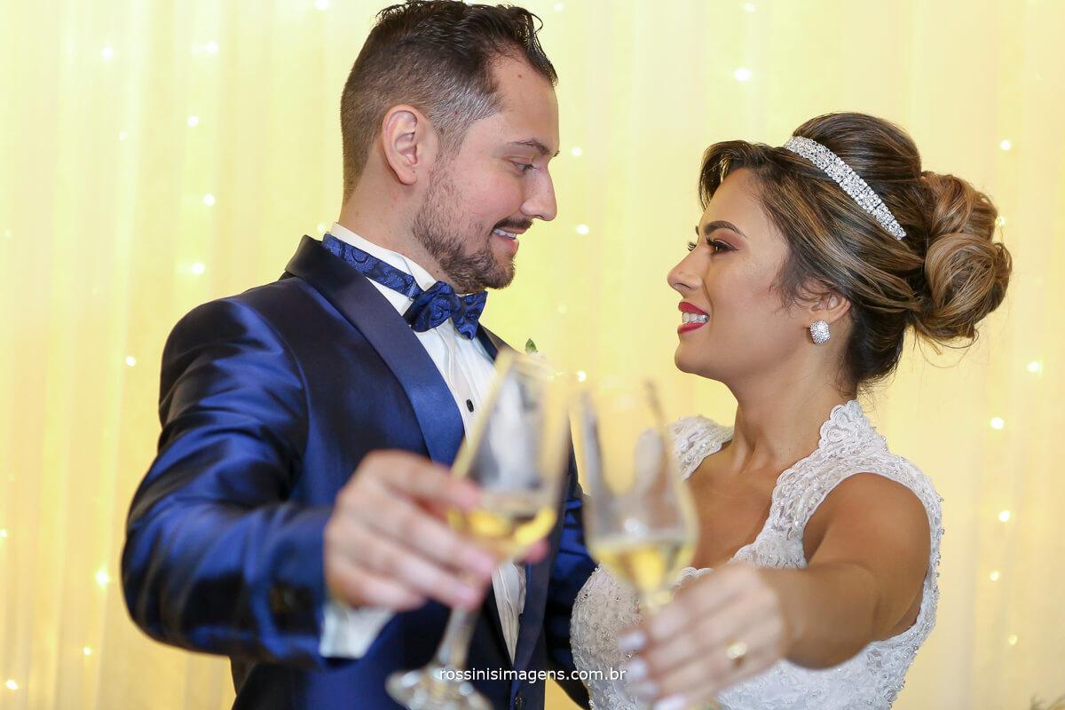 foto rossinis imagens, noivos fazendo o brinde na mesa do bolo com taca de champanhe