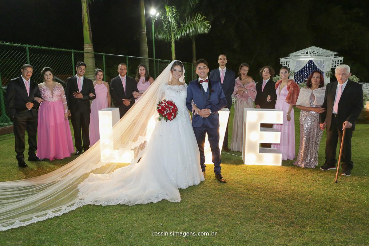 fotografia coletiva dos noivos com os padrinho na frente do letreiro love