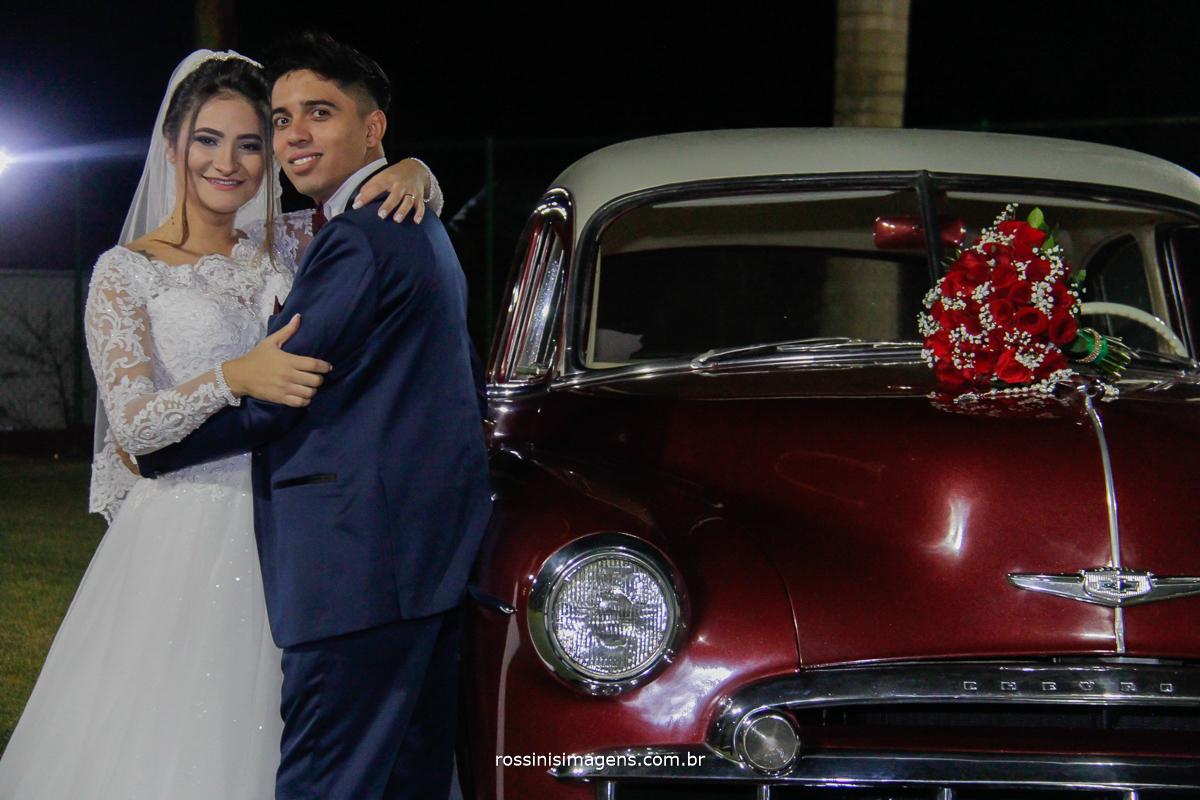 noivos abraçados encostados no carro vermelho