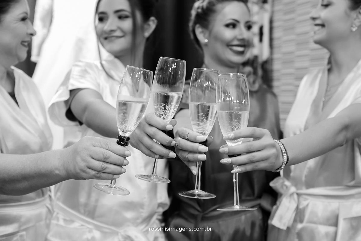fotografia de noiva no making of, dia da noiva fazendo um brinde com a família e as madrinhas,