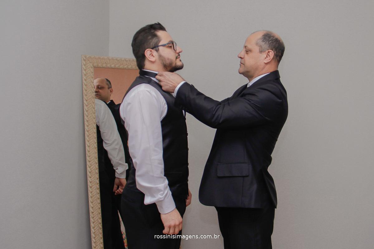 pai colocando gravata no filho para o casamento poá, família unida, união, casamento, casório, rossinis imagens