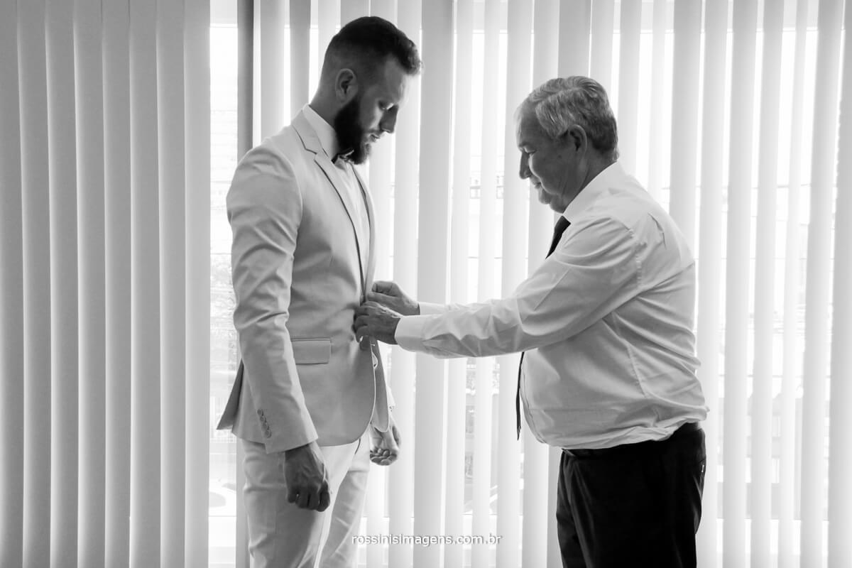 fotografo de casamento em suzano sp rossinis imagens, fernanda e paulo, pai fechando o terno do filho no dia do casamento,