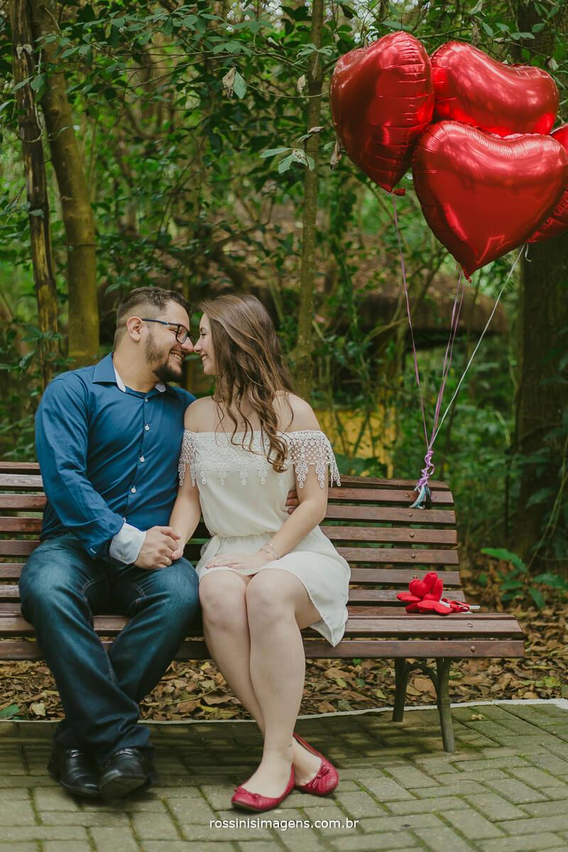 fotografo de ensaio pre casamento em Guararema sp rossinis imagens, casal sentados no banco, namorando, com baloes de gas helio de coração