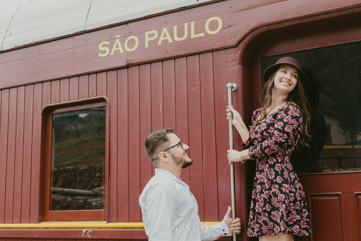 fotografo de ensaio pre casamento em Guararema sp rossinis imagens, noiva no vagão da maria fumaça em Guararema mostrando seu charme ao noivo que esta a olhar-la apaixonadamente