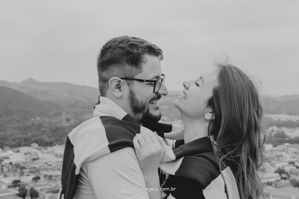 fotografo de ensaio pre casamento em Guararema sp rossinis imagens, noiva enrolando o noivo em seu cachecol do harry potter no mirante, ensaio inspiração, ensaio criativo, ensaio diferente