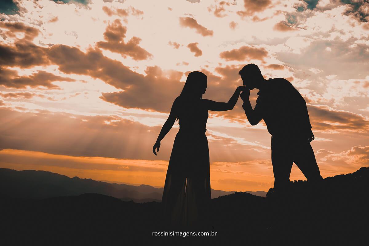 fotografo de ensaio pre casamento em campos do jordao sp rossinis imagens por do sol sensacional noivo beijando a mao da noivo na sessão de fotos