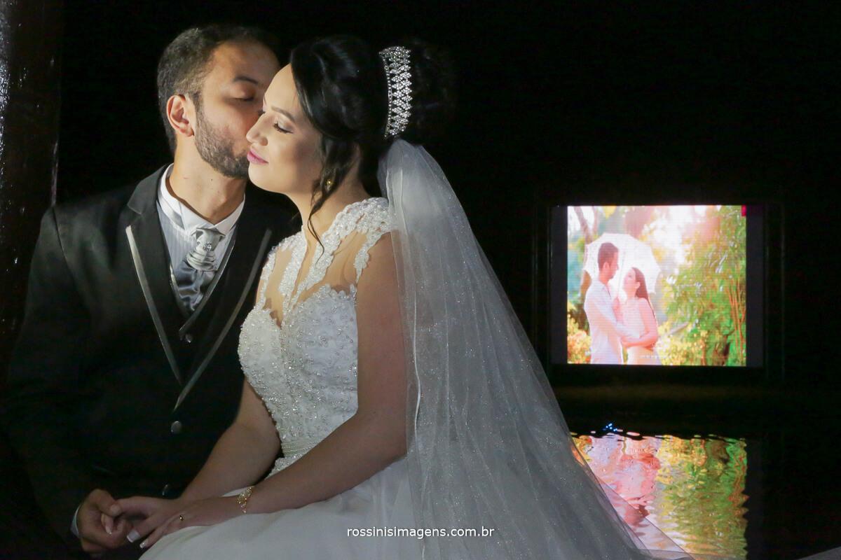 fotografo de casamento em aruja-sp Rossinis Imagens, fotografia de casamento noivos na frente e telao de led ao fundo com foto do ensaio pre casamento