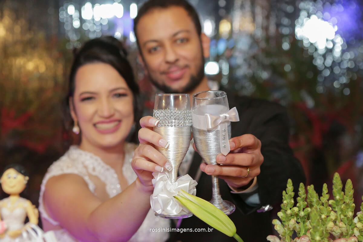 fotografo de casamento em aruja-sp Rossinis Imagens, mesa do bolo com os noivos fazendo um brinde com champanhe