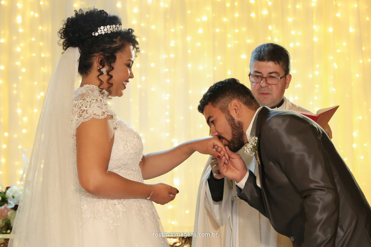 noivo colocando a alianca na noiva no altar