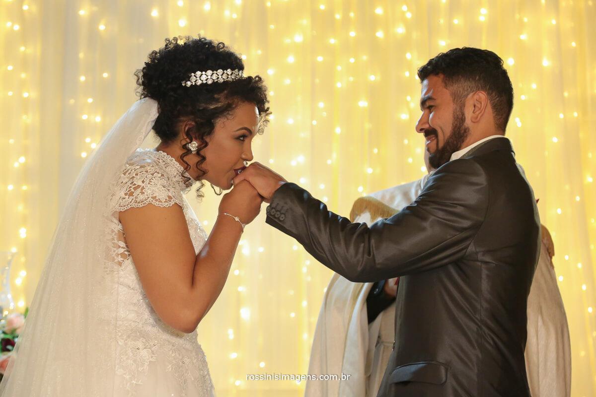 noiva beijando a alianca do noivo no altar