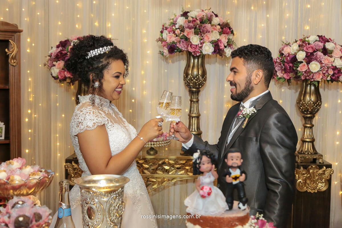 brinde dos noivos na mesa do bolo, fotografia de casamento rossinis imagens