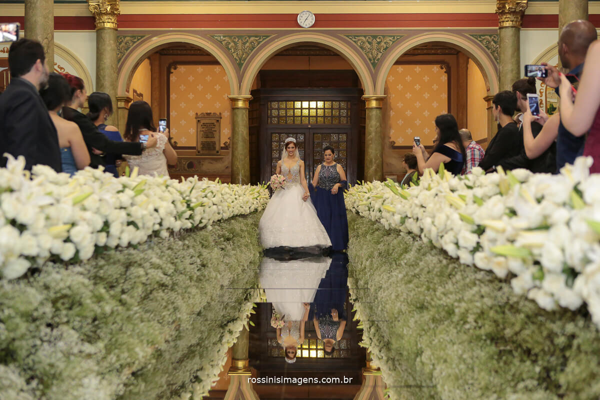 fotografia da noiva entrando acompanhada de sua mãe noiva de vestido top de pedraria e mãe de vestido longo azul lindo