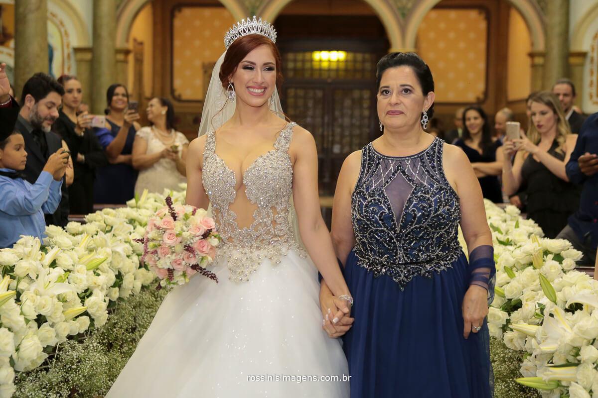 sorriso da noiva na entrada junto com a mãe