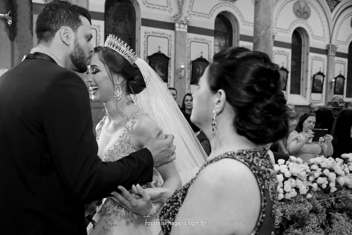 noivo diogo beijando a testa da noiva no altar, começo da cerimonia de casamento noivos na igreja