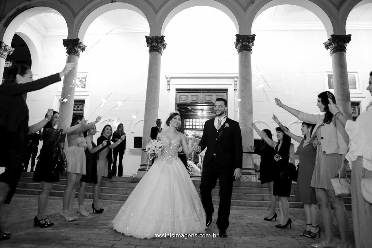 fotografia de casamento preto e branco dos noivos na porta da igreja com os padrinhos