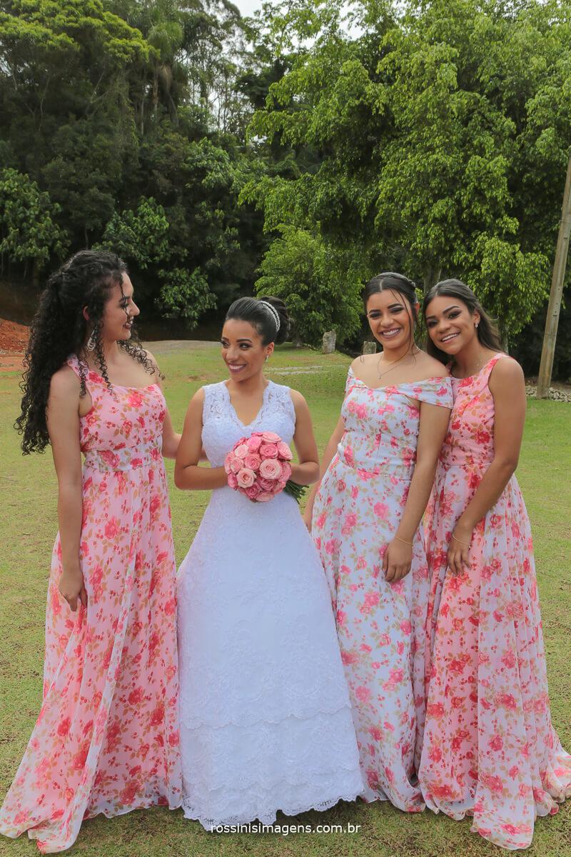 damas adultas e a noiva com seus vestidos floridos e noiva de branco com buquê