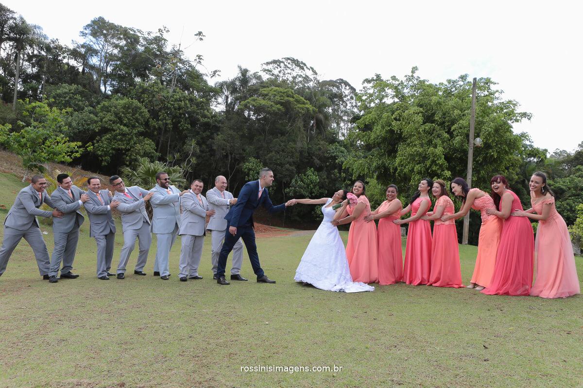 fotografia coletiva com os padrinhos puxando o noivo e as madrinhas puxando a noiva fotografia diferente, inspiração